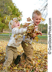 Two Young Children Throwing Fall Leaves Outside