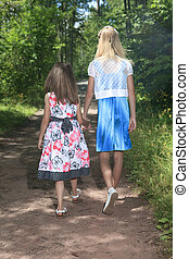 Two young children walking on path holding hands