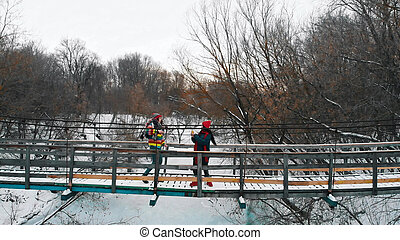Two young colorful women standing on the snowy bridge in winter forest