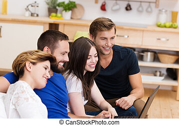 Two young couples sharing a laptop