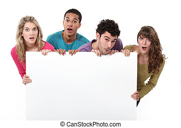 Two young couples stood with advertising board