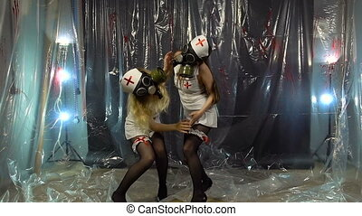 Two young dancing nurses in gas mask