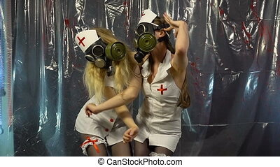 Two young dancing women in gas mask