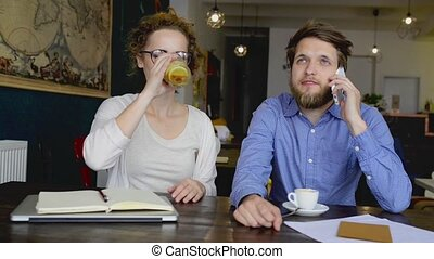 Two young designers on a meeting in cafe. - Two young...