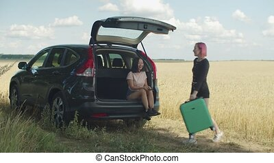 Two young diverse women with suitcases on car trip -...