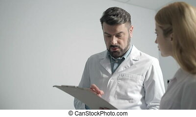Two young doctors talking about treatment results