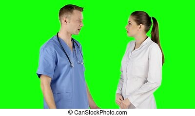 Two young doctors talking together. Green screen