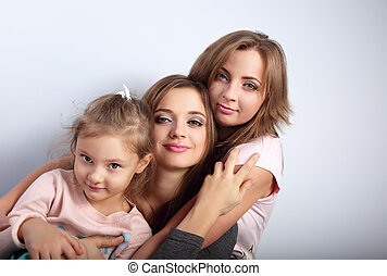 Two young emotional beautiful smiling women and happy joying fun kid girl hugging with love on blue background