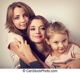 Two young emotional beautiful smiling women and happy joying fun kid girl hugging with love. Toned closeup portrait