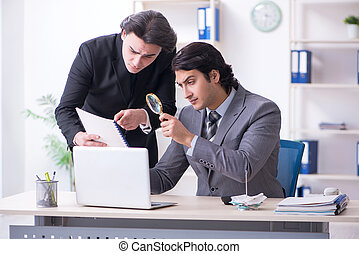 Two young employees working in the office