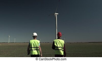 Two Young Engineers Men Approach A Windmill Power Generator...