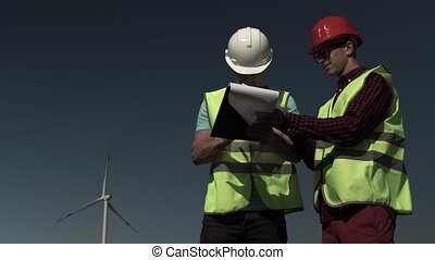 Two Young Engineers Men Approach A Windmill