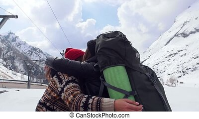 Two young excited women travelers happily hug each other in...