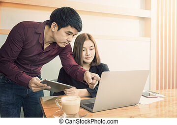 Two young executives, male and female, looking at their computer and making decision