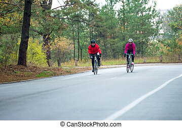 Two Young Female Cyclists Riding Road Bicycles in the Park in the Cold Autumn Morning. Healthy Lifestyle.