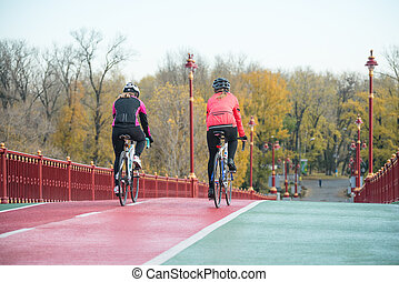 Two Young Female Cyclists Riding Road Bicycles on Bridge Bike Line in Cold Autumn Day. Healthy Lifestyle Concept.