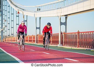 Two Young Female Cyclists Riding Road Bicycles on Bridge Bike Line in Cold Sunny Autumn Day. Healthy Lifestyle Concept.