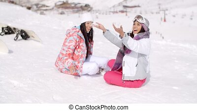 Two young female friends chatting in the snow
