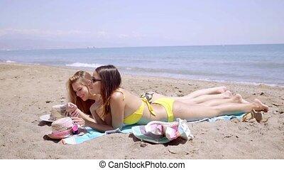 Two young female friends sunbathing in bikinis