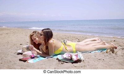 Two young female friends sunbathing in bikinis on the golden...