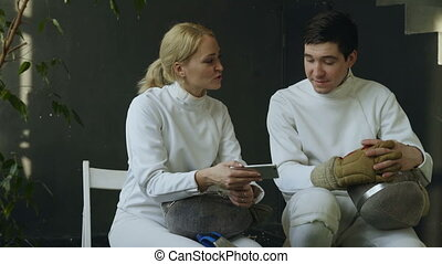 Two young fencers man and woman watching fencing competition on smartphone and sharing experience after training indoors