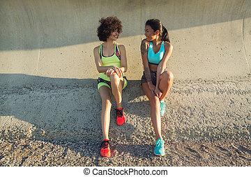 Two young fitness women in sportswear talking