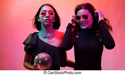 Two young flirting cute Asian women in black bodysuits and sunglasses playfully disco dancing for camera on colorful bright lights