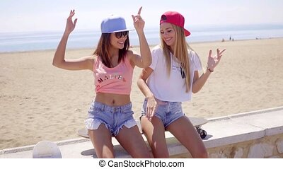 Two young friends in shorts sitting near beach