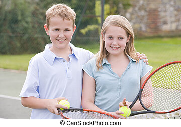 Two young friends with rackets on tennis court smiling