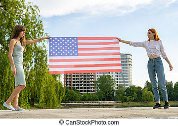 Two young friends women holding USA national flag in their hands at sunset. Patriotic girls celebrating United States independence day. International day of democracy concept.