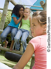 Two young girl friends at a playground whispering about...
