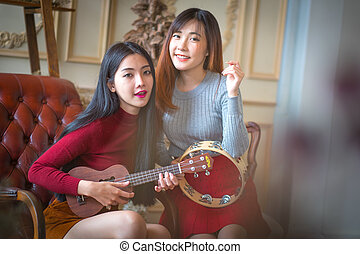 Two young girl friends having fun and smiling and Playing Guitar and instruments.