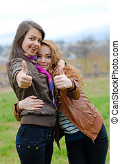 Two young girl friends showing thumbs up in autumn park