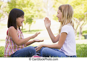 Two young girl friends sitting outdoors playing patty cake...