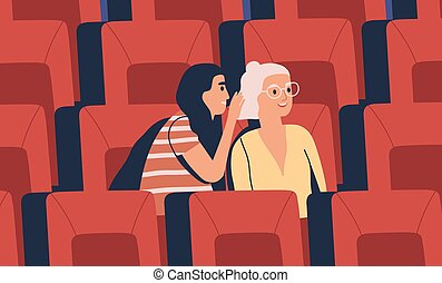 Two young girl friends whispering at movie theater. Women ...