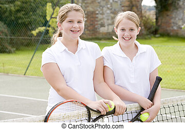 Two young girl friends with rackets on tennis court smiling