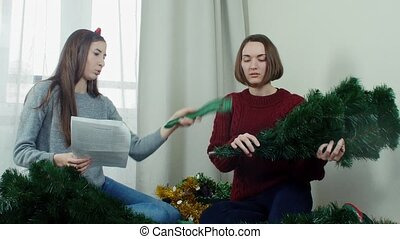 Two young girl preparing Christmas tree for decorations and having fun New year