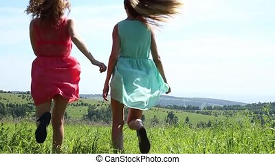 two young girlfriend running hand in hand on the green meadow