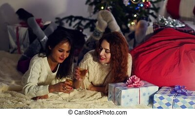 young girlfriends girlfriends, a brunette and a redhead lay on a rug near the Christmas tree and drink Shompanskoe. Against the backdrop of the girls, a Christmas tree in red tones