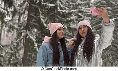 Two young girlfriends make selfie on the background of the winter forest using a smartphone. 4K