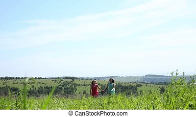 Two young girls are running on a field hand in hand, freedom and relationship concepte