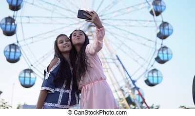 Two young girls do selfie using smartphone while standing on the background of a Ferris wheel. slow motion.