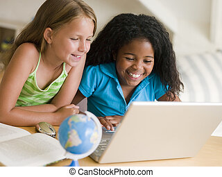 Two Young Girls Doing Their Homework On A Laptop