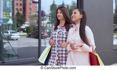 Two young girls go after shopping holding shopping bags. slow motion. HD