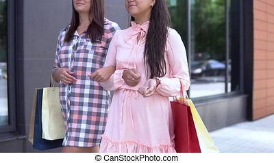 Two young girls go after shopping holding shopping bags. slow motion.