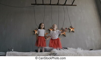 Two young girls happily jump on the bed, holding boxes with gifts in their hands. Having fun together at winter holiday time. Merry Christmas and Happy Holidays