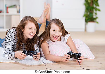 Two young girls happily playing video games