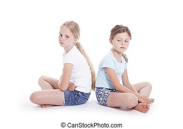 two young girls having a disagreement in studio with white...