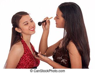 Two young girls having fun putting make up