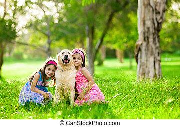 Two young girls hugging golden retriever dog